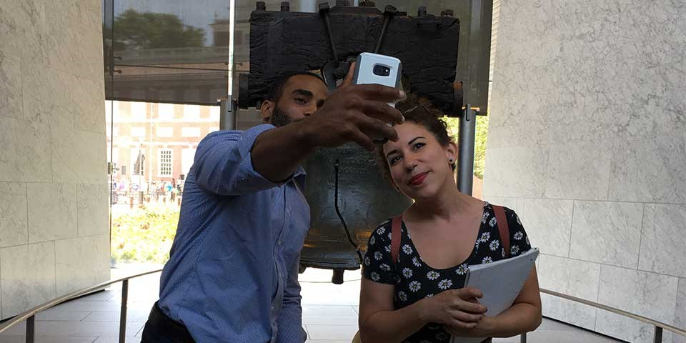"Color photo of a man and woman taking a ""selfie"" photo in front of the Liberty Bell."