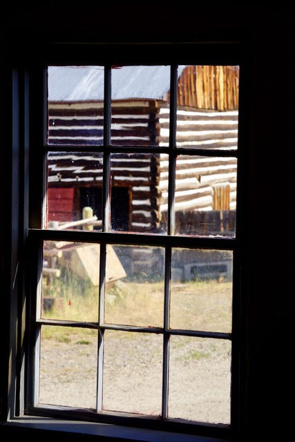Log draft horse barn through the window pane of the bunkhouse.