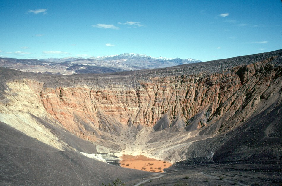 A large crater in multi-hued desert stone, stretching 600 feet deep and a half mile across.