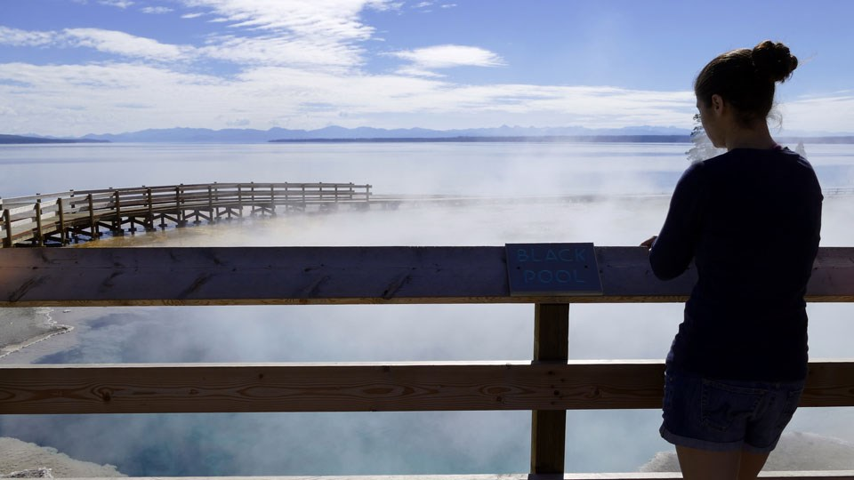 "Woman stands by wooden sign that says ""Black Pool"" and looks at the blue, steaming hydrothermal pool"