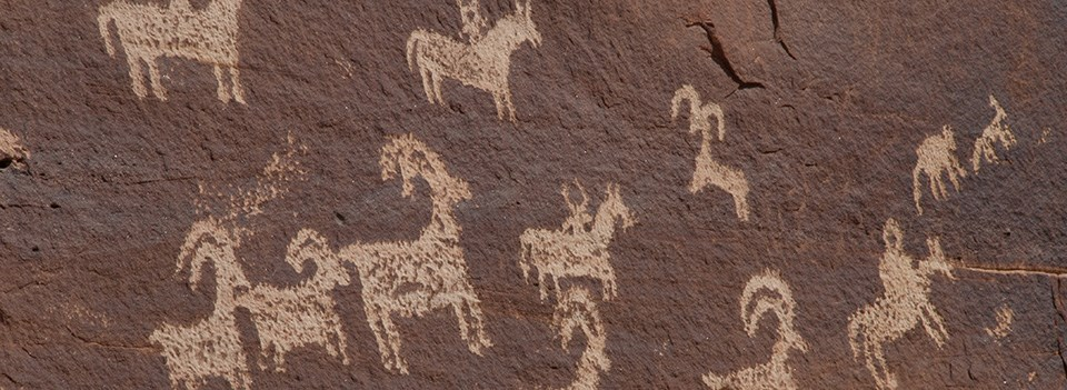 figures of sheep and riders on horseback carved on a rock wall