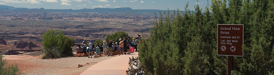 a paved sidewalk leads to a group of people standing at a viewpoint