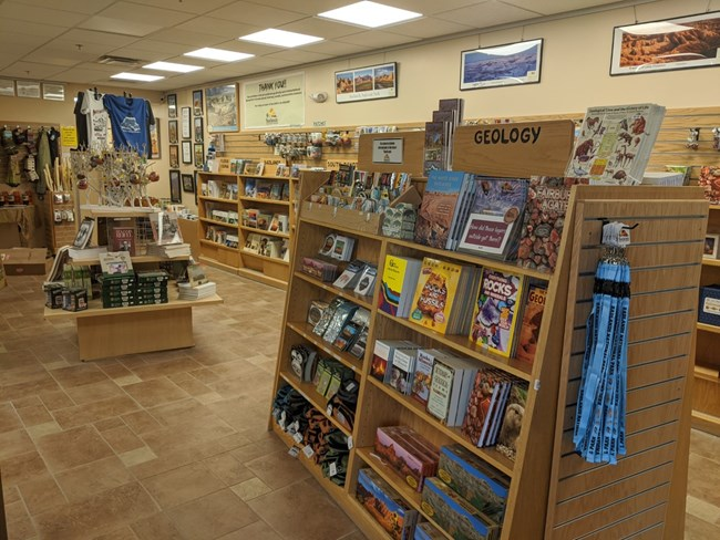 a store filled with stocked bookshelves, souvenirs, and t shirts.
