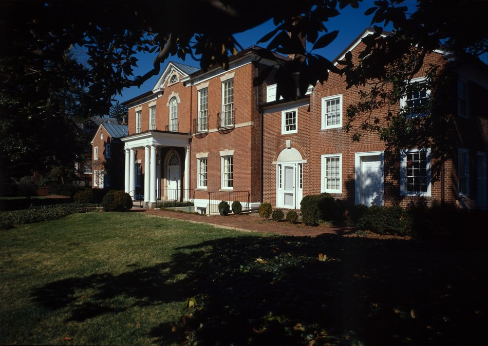 Color photograph of the outside of the Dumbarton House, made of red brick.