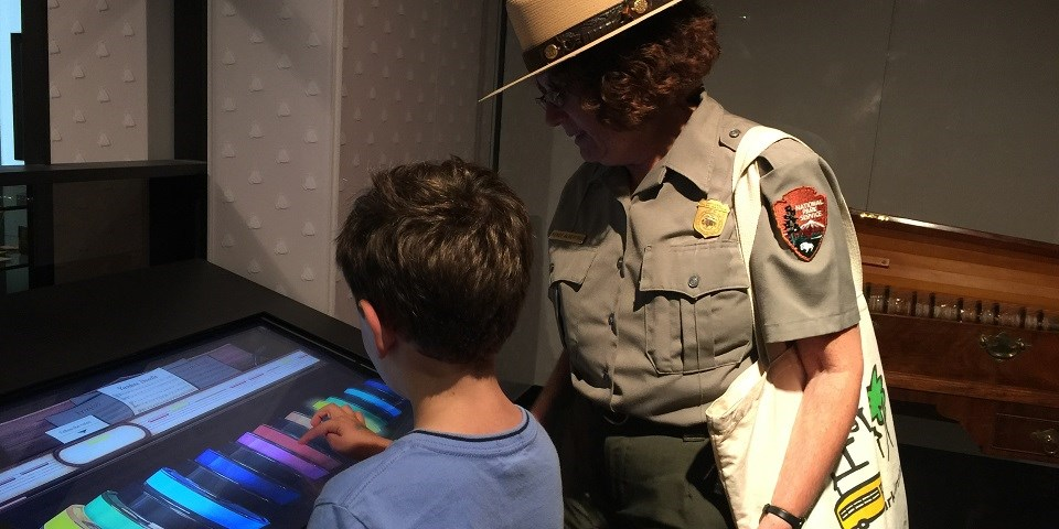 Color image of a child playing a virtual glass armonica on a computer screen as a ranger watches.