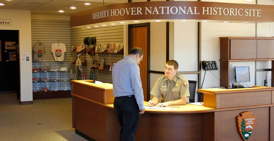 A ranger at an information desk assists a park visitor.