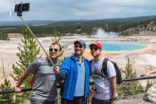 Three visitors take a selfie in front of a colorful hot spring.