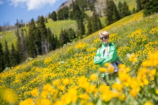 A boy sites on a slope filled with yellow wildflowers