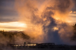 Beautiful reds and golds color a sunset over a boardwalk with a geyser erupting in the background.