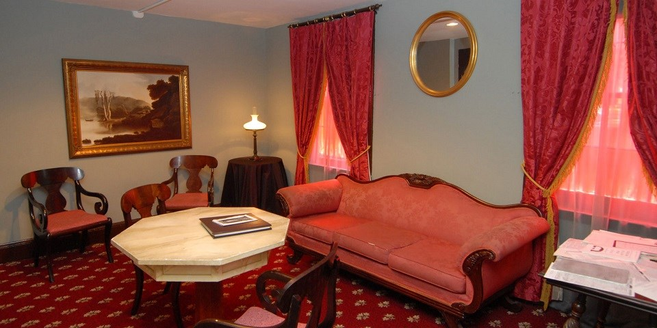 Color image of a room decorated with 19th-century furnishings that include red carpet, red couch, and red curtains.