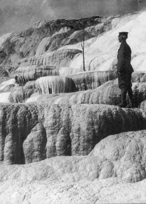 A US Army soldier stands on the Mammoth Hot Springs terraces, watching over Pulpit Spring