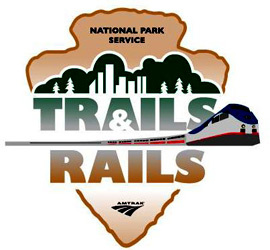 Trails & Rails logo with a National Park Service Arrowhead with an Amtrak train through the middle.