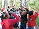 A ranger points out a bird to students with binoculars