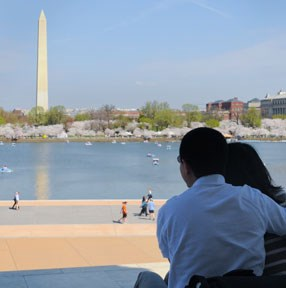 couple at right sites on Jefferson steps overlooking tidal basin and washington monument