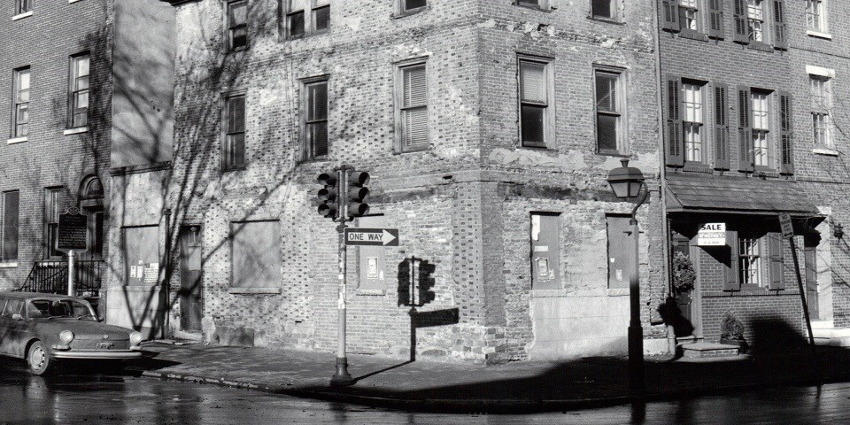 Detail from a black and white photo (circa 1960) showing the exterior of a brick house situated on a corner lot with a car parked next to the building.