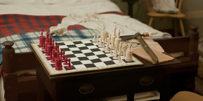 Close-up of a chess board, tomahawk, and a pair of glasses on a table.