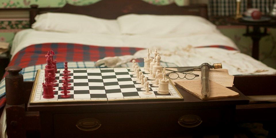 Color photo showing a replica of an 18th-century chess set and glasses on a wooden dresser at the foot of a wooden bed.