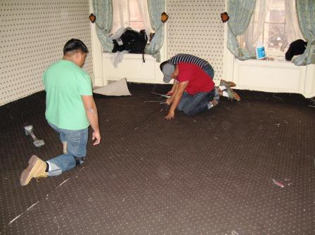 Laying down new carpet in the master bedroom.