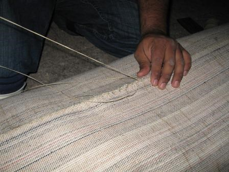 Hand-sewing of carpet sections.