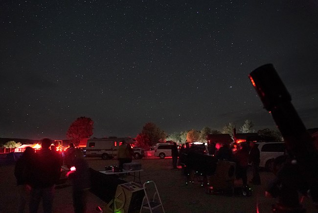 stargazers gather in a field of telescopes lit by red lights to look up at the starry sky
