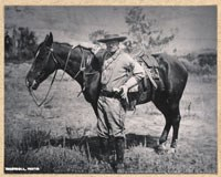 Theodore Roosevelt with his horse in the badlands.