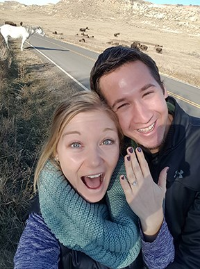 A newly engaged couple shows off an engagement ring with park wildlife in the background