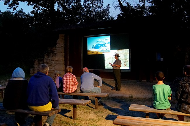 A ranger stands in front of a projection screen while visitors sit on amphitheater benches