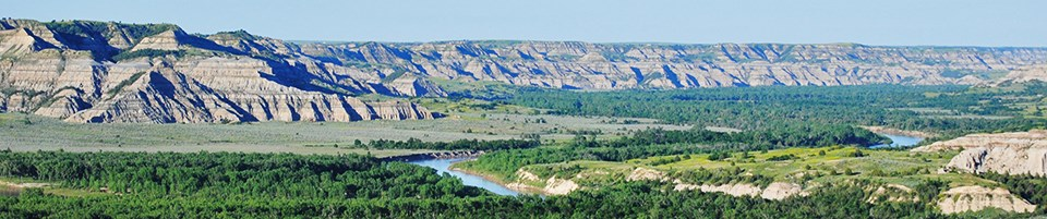 Tan and grey stripped buttes rise up from a wide green valley with a blue, winding river.