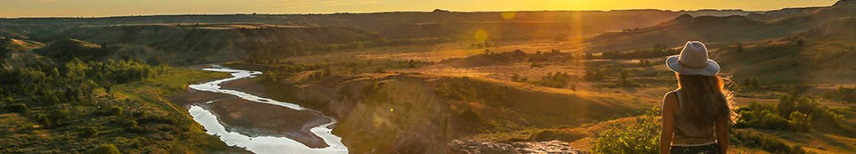 A woman in a western style hat looks out across the Little Missouri River and badlands bathed in the sunset's golden light.