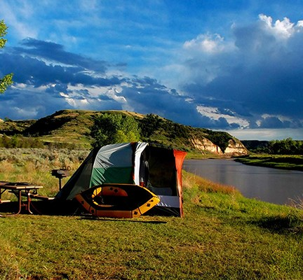 A brightly colored tent sits on a bank above the Little Missouri river with sun-bathed buttes in the background.