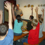 NPS Ranger with class of students all raising their hands to participate
