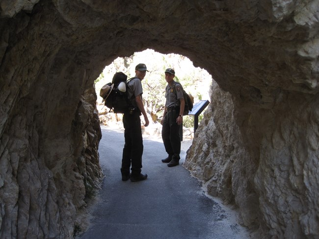 People-rangers at tunnel on trail