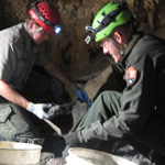 Rangers work to restore Middle Cave Lake, taking out many 5-gallon buckets of debris to reach the natural cave floor.