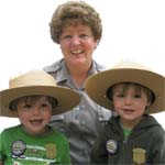 Two new Junior Rangers show off their badges while our ranger lends some real ranger hats to try on!