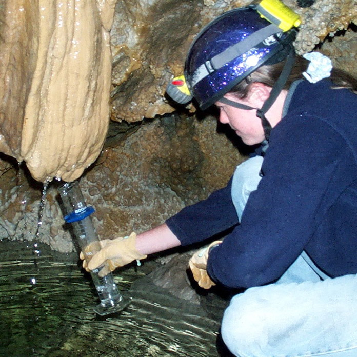 Collecting a water sample from a stalagtite for analysis.