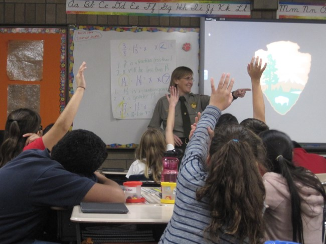 Smiling ranger calls on child with raised hand in classroom setting