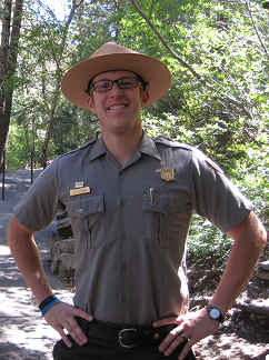 Ranger stands on paved hiking trail facing the camera with hands on hips. Green trees in background.