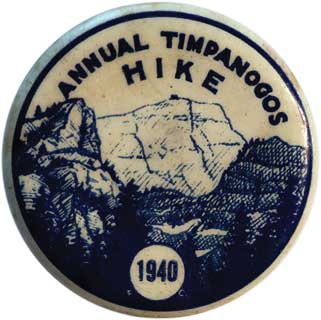 Blue and cream colored lapel pin from the 1940 Annual Mount Timpanogos Hike featuring a graphic of Mount Timpanogos.