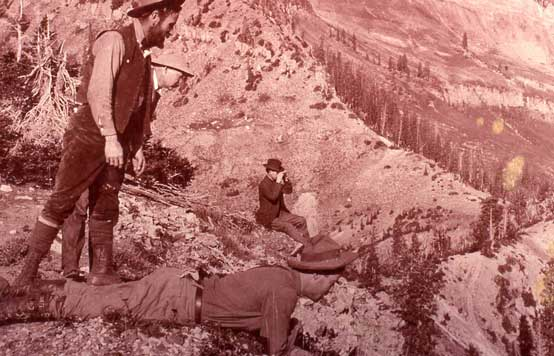 George Tyng and his two sons, Francis & Charles, looking into Mineral Basin.  CH Joy is the photographer looking through binoculars. Reddish toned, black and white image with big views from Miller Hill.