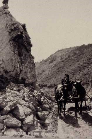 George Tyng sitting on the wagon with two horses at Split Rock, American Fork Canyon, trying to convince photographer CH Joy to get his son down from climbing on the rock.