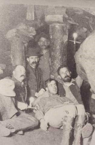 George Tyng with his hat on his knee and his two sons sitting beside each other.  CH Joy the photographer is sitting in the middle behind George.  One of George's miners is visible in the background by the candle reflection light. All the men are surrounded by what appear to be mining timbers inside of a rock tunnel.