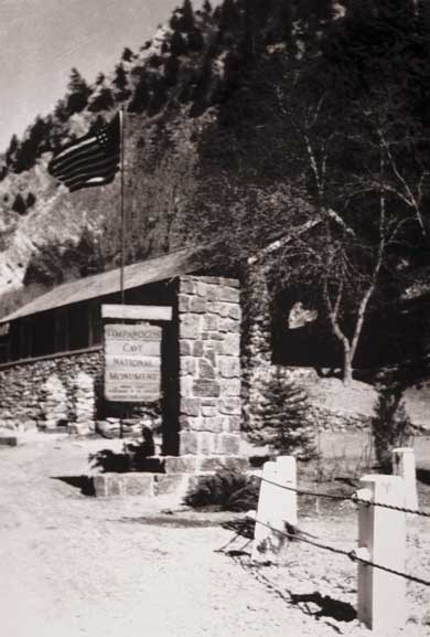 Black and white view of the historical visitor center featuring stacked rock walls and an entrace sign column.