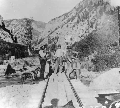 Black and white of photo of several men and a horse, centered on the tracks of the American Fork Canyon Railway in the 1870s.