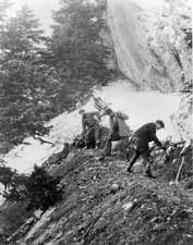 "The Timpanogos Cave Committee sponsors the building of the trail to the caves which workers ""carve"" out of the cliffside. The three men pictured here are working with handtools to create a path."
