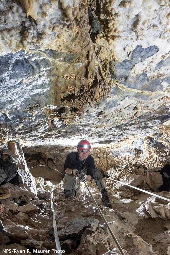 Caver sits smiling while holds onto a rope handline in Hansen Cave, surrounded by rocks