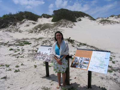 Graphic design intern Ximena Vergara stands at the sand dune with the exhibit panels she designed.
