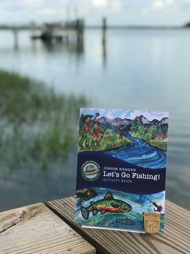 a jr ranger booklet on fishing with water and a dock in the background