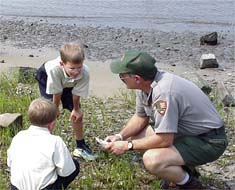 Children and a ranger look at items found along the riverfront.