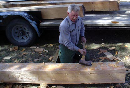 A preservation staff member is hewing a sill beam for the historic kitchen house.