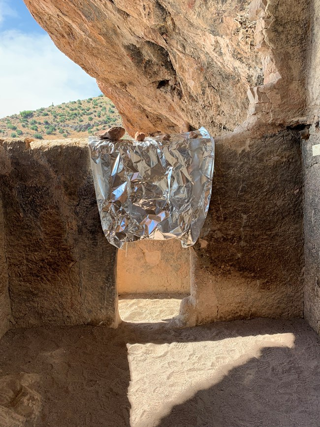 cliff dwelling door wrapped to prepare for wildfire